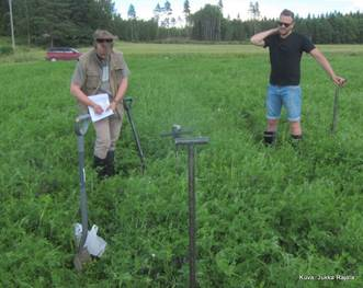 Otto Hyssälä (oik) seuraa OSMO-hankkeen tutkijan Tuomas Mattilan (vas) havaintojen tekoa maan kasvukunnosta. Kuva: Jukka Rajala 19.7.2016.